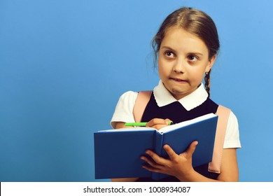 Pupil in school uniform with braid. Girl writes in big blue notebook. School girl with thoughtful face on blue background, copy space. Back to school and education concept