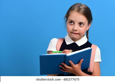 Pupil in school uniform with braid. Girl writes in big blue notebook.