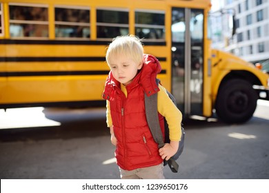 Pupil with schoolbag with yellow school bus on background. Back to school.