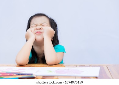 Pupil self isolating herself in doing art homework. Child bored or frustrated and frantic face. Kid pull their faces with both hands. Girl stay at home during covid-19 lockdown. Social Distance.