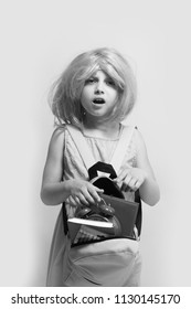 Pupil with surprised face expression, isolated on light pink background. Kid with alarm clock and books. Girl with wig in pink dress with backpack. Back to school and learning concept.