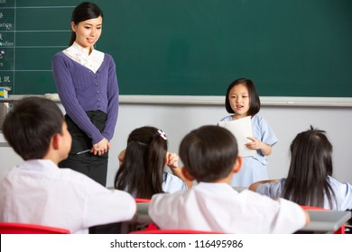 Pupil And Teacher Standing By Blackboard In Chinese School Classroom