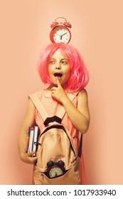 Pupil with thoughtful face expression, isolated on light pink background. Back to school and learning concept. Girl with wig in pink dress with backpack. Kid with alarm clock on head and books in hand
