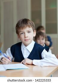 Pupil in uniform sitting at  desk in school classroom