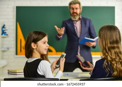 Pupil Wearing Uniform. Little Students Studying And Reading. doing homework writing and reading. children girls and teacher man. Elementary Teacher Giving Support In Classroom. Analyzing strategy.