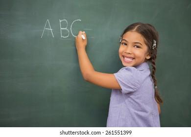 Pupil writing on large blackboard at elementary school