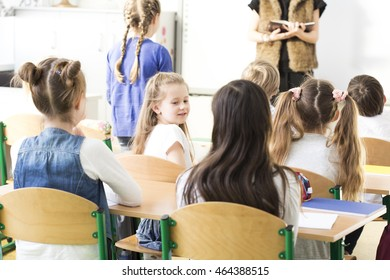 Pupils in the classroom with the teacher asking one girl a question