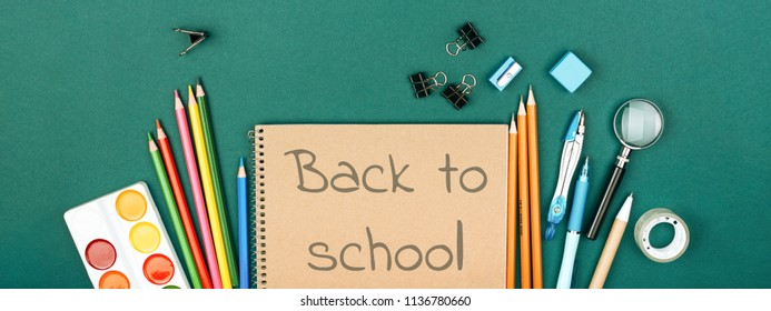 Pupil's desk with stationary and notebook with inscription Back to School on green background. Preparation to school. Banner for website.