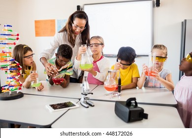 Pupils doing science with a teacher in classroom