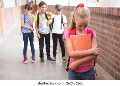 Pupils friends teasing a pupil alone in elementary school