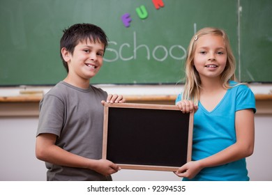 Pupils holding a school slate in a classroom