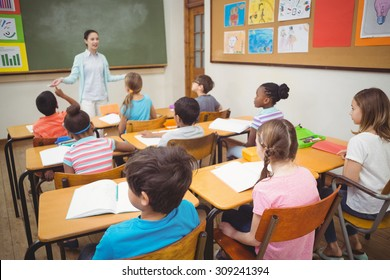 Pupils listening to teacher during class at the elementary school