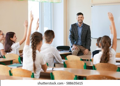 Pupils listening teacher and raising hands to answer in classroom