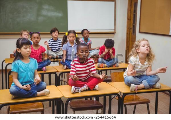 Élèves méditant en position lotus sur un bureau en classe à l'école primaire