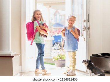 Pupils of primary school. Girls with backpack is going to school from home. Beginning of lessons. First day of fall.