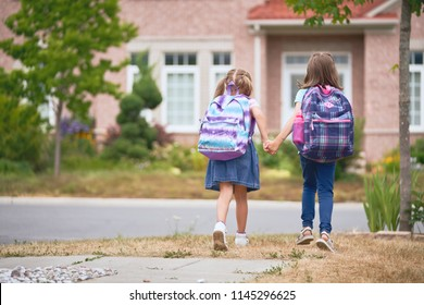 Pupils of primary school. Girls with backpacks near building outdoors. Beginning of lessons. First day of fall.