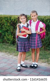Pupils of primary school. Girls with backpacks and books near building outdoors. Beginning of lessons. First day of fall.