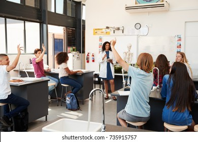 Pupils raising hands in a high school science lesson