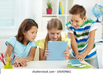 Pupils at school being interested in a new device of their friend