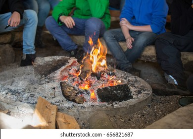 pupils sitting in front of a campfire
