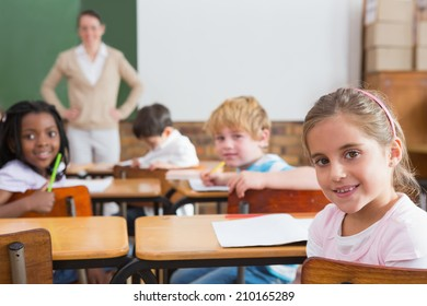 Pupils and teacher smiling at camera in classroom at the elementary school