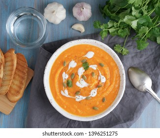 Pupmkin cream soup puree, dietary vegetarian lunch on blue wooden table, top view. Glass of water, toast, parsley, garlic.