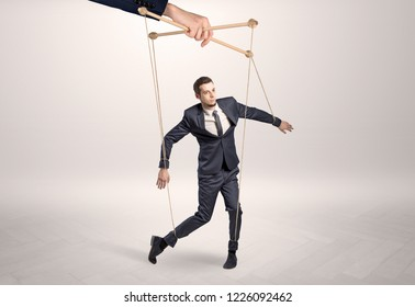 Puppet businessman in an empty room leaded by a huge hand