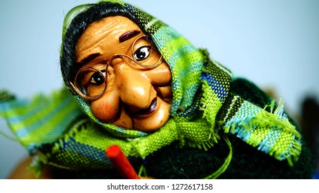 puppet for the epiphany of a old witch with glasses and kerchief on the head. white background, copy space