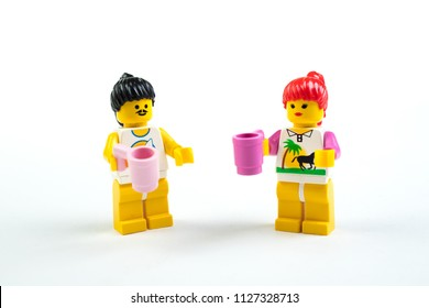 Puppet figurines of lego on white background. Meeting friends, drinking tea