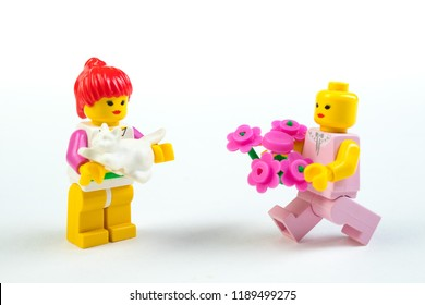 Puppet figurines of lego on white background. A rendezvous, a man gives a woman flowers