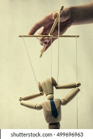 Puppet on a string in the hands of puppeteer. Doll holding on to the head, portraying panic.  Puppet is presented in business style with a tie.