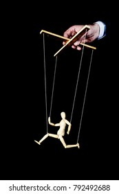 Puppeteer. Wooden doll on strings. The puppet theatre. Running puppet against a black background.