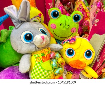 Puppets of a rabbit, a frog and a duckling with chocolate eggs at the market for Easter