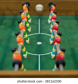 The puppets of Table soccer stand face to face in the center of the field prepare for competition