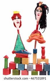 Puppets from the wooden spoon and the castle of colored cubes on a white background