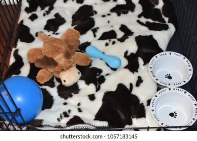 Puppy Crate with Cow Pattern Blanket and Toys and Cute Dishes