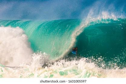 Pupukea, Hawaii, USA - January 26, 2020: Brazilian bodyboarder champion, Guilherme Tamega, takes on the big surf at the world famous Banzai Pipeline surf spot on the North Shore of Oahu.