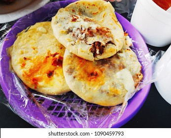 Pupusas of beans and melted cheese in a typical white plate. Typical food of El Salvador in Central America.
