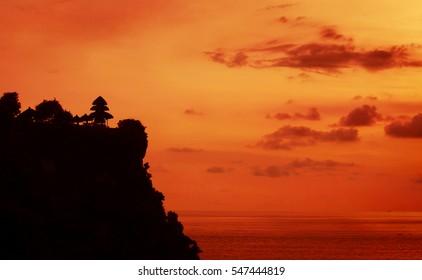 Pura Luhur Uluwatu rock cliff temple at sunset - Bali, Indonesia