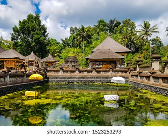 Pura Tirta Empul Temple, Tampaksiring, Bali, Indonesia - October 06, 2019: Green pond at the water temple famous for its holy spring water, where Balinese Hindus go to for ritual purification.