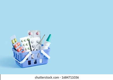 purchase, delivery of medicines to your home. home first aid kit for colds, illnesses, viruses, epidemics. online purchase of medicines. drugs in basket on blue background, copy space - Shutterstock ID 1684711036