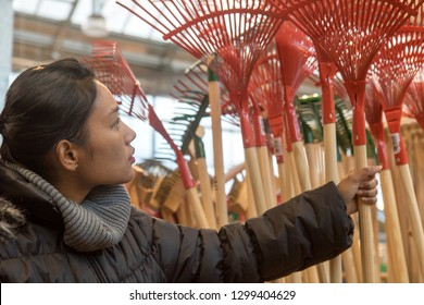 Purchase of garden supplies in a department store. Young woman choosing a rake in a shop.
