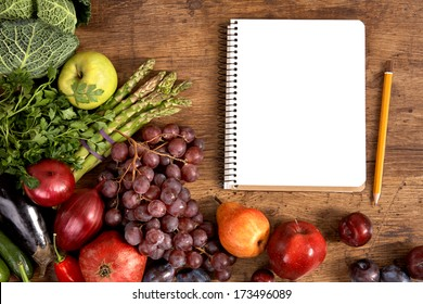 Purchase list. Empty space / studio photography of open blank ring bound notebook surrounded by a fresh vegetables and pencil on old wooden table