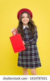 Purchase the trend. Little girl smiling with personal purchase on yellow background. Happy small child holding her purchase in red paperbag. Buying fashion purchase for kids.