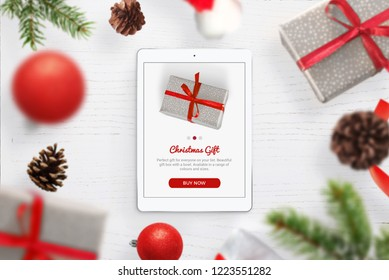 Purchasing Christmas gifts online. Tablet on the table, surrounded by Christmas gifts and decorations.
