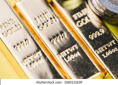 Pure 999.9 shiny fine gold bullions ingot bars with money coins, closed up macro shot as financial asset, investment and wealth concept.
