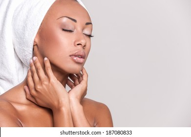Pure beauty. Beautiful young Afro-American shirtless woman touching her face and keeping eyes closed while Isolated on gray background