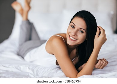 Pure beauty. Beautiful young woman adjusting her hair and looking at camera while lying on the bed at home