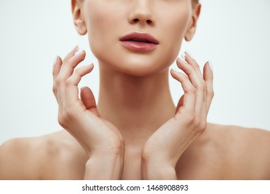 Pure beauty. Cropped photo of young blonde woman touching her soft and fresh skin while standing against grey background. Skin care
