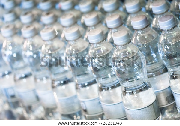 Pure bottled water in small handy bottles for sale on store shelfs. Close up horizontal composition with shallow depth of field.